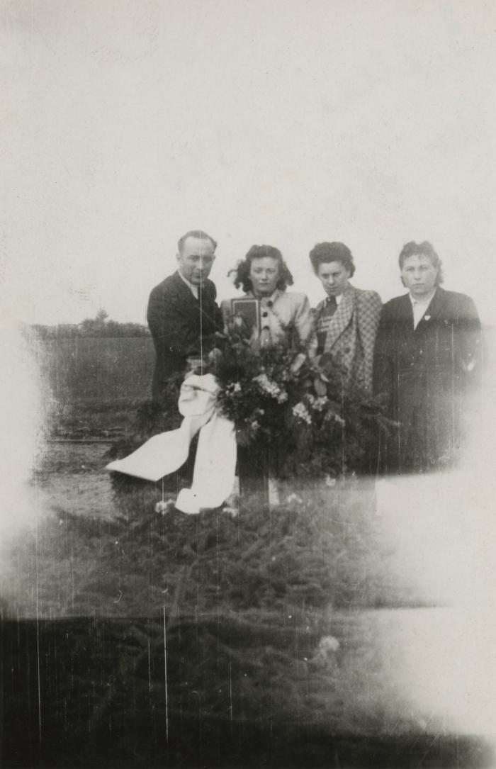 [Photograph of unidentified man and three women with flower wreath]