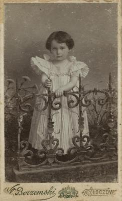 [Photograph of unidentified child wearing white dress]