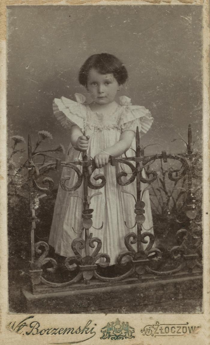 [Photograph of unidentified child wearing white dress]