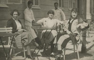 [Photograph of three unidentified women sitting in restaurant patio area]