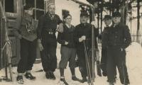 [Photograph of six unidentified men standing in snow with skis]