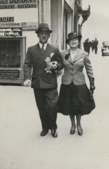 [Photograph of Leo and Julia Schmucker walking in street]