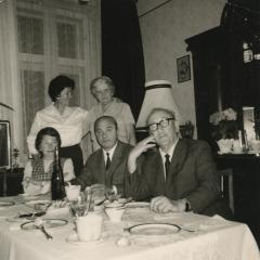 [Photograph of Leo and Julia Schmucker at table with unidentified people]