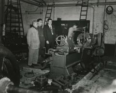 [Photograph of Manfred Gottfried with three unidentified men in a room full of machinery]