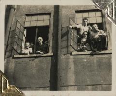 [Photograph of eight unidentified people leaning out of windows]