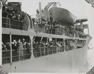 [Photograph of people waving from the deck of a ship]