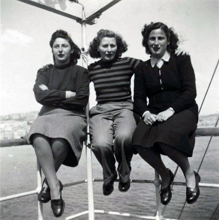 [Photograph of Gerda Kraus, Lori Seemann, and a woman sitting on the railings of a ship]