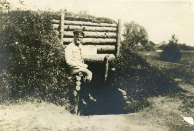 [Alfred Meyer sitting alone in the field while serving in the army]