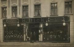 [Photograph of two men and dog in front of S. Bick store]