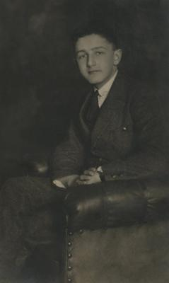 [Photograph of unidentified young man sitting in chair]